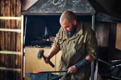 Blacksmith working in the forge. Manufacture of parts and weapons from molten metal, using the hammer and anvil. Blacksmith working in the forge. Manufacture of Royalty Free Stock Photo