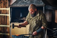 Blacksmith working in the forge. Manufacture of parts and weapons from molten metal, using the hammer and anvil. Blacksmith working in the forge. Manufacture of Stock Image
