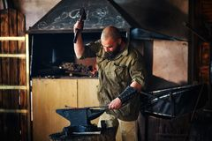Blacksmith working in the forge. Manufacture of parts and weapons from molten metal, using the hammer and anvil. Blacksmith working in the forge. Manufacture of Stock Photo
