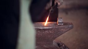 Blacksmith working with hammer and hot red metal. Two mans forge the iron on the anvil in smithy. stock video footage