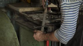 Blacksmith is working with iron detail and using a file. Blacksmith is working with iron detail on vise grip on blacksmith table and using a file stock footage