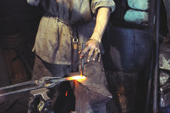 Blacksmith working on metal on anvil at forge high speed Royalty Free Stock Photo