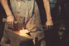 Blacksmith working metal with hammer Stock Photography