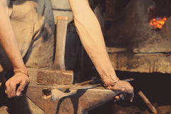 Blacksmith working metal with hammer Royalty Free Stock Photography