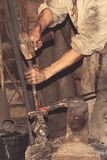 Blacksmith working metal with hammer Stock Images