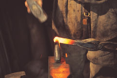 Blacksmith working metal with hammer Royalty Free Stock Image