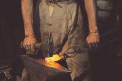 Blacksmith working metal with hammer on the anvil. In the forge Royalty Free Stock Photos