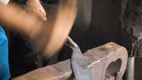 Blacksmith working metal with hammer. stock footage
