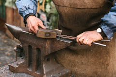 Blacksmith working metal with a hammer on the anvil in the forge Royalty Free Stock Photography