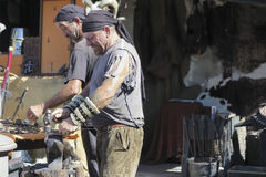 Blacksmith working outdoor. S during recreation of a medieval market. Photo taken on 10 October 2015 in Alcalá de Henares, Madrid, Spain Royalty Free Stock Image