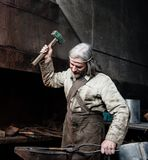 Blacksmith working in the smithy.  Stock Image