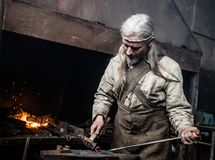 Blacksmith working in the smithy.  Royalty Free Stock Images