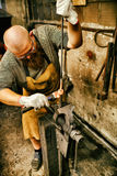 Blacksmith working in workshop Stock Photography