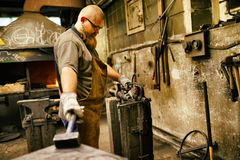 Blacksmith working in workshop Stock Images
