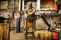 Blacksmith working in workshop Royalty Free Stock Images