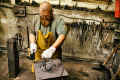 Blacksmith working in workshop Stock Image