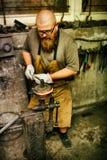 Blacksmith working in workshop Stock Photos