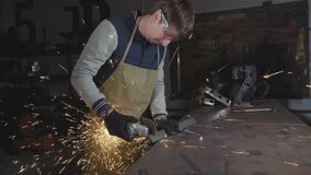 Blacksmith working in a workshop with metal via angle grinder, slow motion. Sparks during cutting of metal angle grinder. Blacksmith working in a workshop with stock video