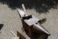 Blacksmith works the iron with anvil and hammer royalty free stock images