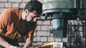 The blacksmith works with the item is removed from the fire Royalty Free Stock Images