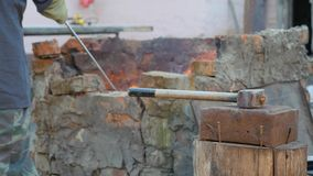Blacksmith works metal. Craftsman, the highlander on private smithy in the village. Sledgehammer lies on the anvil