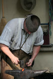 Blacksmith works with tools on the anvil Royalty Free Stock Photography