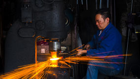 Blacksmith workshop. In China`s Songyang Town, Zhejiang Province, the old street still retains some hand workshops, the blacksmith artisans are using the machine
