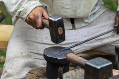 Blacksmithing, σιδηρουργός στο άσπρο αμόνι χτυπημάτων υφασμάτων με ένα σφυρί Στοκ φωτογραφία με δικαίωμα ελεύθερης χρήσης