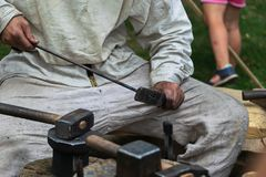 Blacksmithing, σιδηρουργός στο άσπρο ύφασμα κοντά στο αμόνι Στοκ Εικόνα