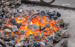 Blacksmithing, metal horseshoe is heated in the forge Royalty Free Stock Image