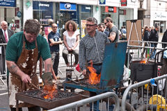 Blacksmiths demonstrate their work. Visitors watch members of the ancient, traditional Worshipful Company of Blacksmiths demonstrate their work in the street at Royalty Free Stock Images
