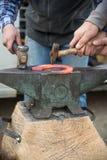 Blacksmiths forging an incandescent horseshoe Stock Photography