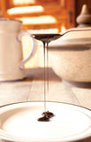 Blackstrap molasses. Drizzling from a teaspoon Royalty Free Stock Photography