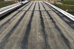 Blacktop stripes on the ground base. Renewal of bridge over the channel near Cetina river, groundwork prepared for asphalt Stock Image