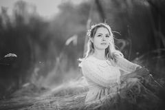 Blackwhite photo girl is sitting in the field on the sunset background Stock Image