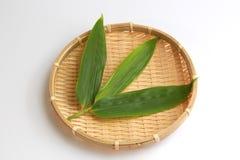 Blad av den japanska lösa ingefäran på bambukorgen Fotografering för Bildbyråer