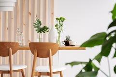 Blad i vaser på den långa trätabellen i moderiktig vit matsal royaltyfria foton