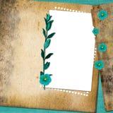 Blad met bloemen op oude grungeachtergrond Royalty-vrije Stock Afbeeldingen