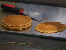 Blad met deegcrumbs, vers gebakken Stroop-wafels, Nederlandse stijl, op de vage achtergrond een heftoestel stock fotografie