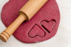 Blad rood deeg met een deegrol en verwijderd twee koekjes van de hartvorm, die voor de Dag van Valentine voorbereidingen treffen Royalty-vrije Stock Foto's