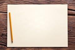 Blad van document en potlood op oude houten lijst. Stock Foto