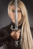 The blade of fashion. The beautiful photo of woman holding the sword Royalty Free Stock Photos