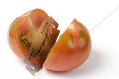 The Blade and the Tomato. Razor blade isolated over a white background cutting a tomato stock images