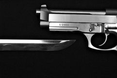 Blade under pistol. A black and white image of a sword underneith a pistol Royalty Free Stock Photo