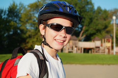 Blader Boy 1. A nine year old boy wearing sunglasses, a bike helmet and a backpack stands in a sunny park with climbing equipment in the background stock photography