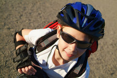 Blader Boy 2. A nine year old boy wearing sunglasses, a bike helmet and a backpack crouches in a sunny park royalty free stock photography