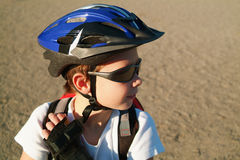 Blader Boy 3. A nine year old boy wearing sunglasses, a bike helmet and a backpack crouches in a sunny park stock images