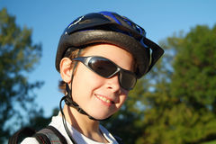Blader Boy 4. A nine year old boy wearing sunglasses, a bike helmet and a backpack stands in a sunny park with trees and blue sky in the background stock photography