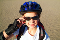 Blader Boy 5. A nine year old boy wearing sunglasses, a bike helmet and a backpack crouches in a sunny park royalty free stock photo