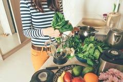 Bladeren van de handen tearing spinazie in een mixerkom stock afbeeldingen